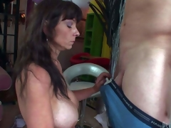 Mature lengthy haired brunette doxy with gigantic fake mounds and good looking body seduces young chap with meaty sausage and gives him lusty oral in living room in close up