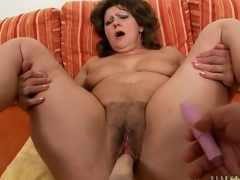 Dildo machine fucks deep into curly cunt